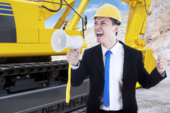 Businessman with megaphone and excavator Royalty Free Stock Image