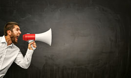 Businessman with megaphone in hand. Angry young man shouting megaphone on grunge background Royalty Free Stock Photos