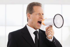 Businessman with megaphone. Portrait of confident mature man in formalwear shouting at megaphone while standing near window Stock Photos