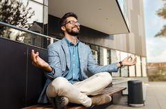 Businessman - mentally preparing for business meeting. Sitting in meditation pose in front of office building and smiling royalty free stock images