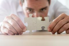 Businessman merging together two matching puzzle pieces royalty free stock photography