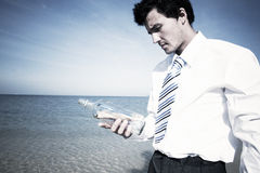 Businessman with message in a bottle Stock Images