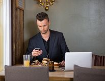 Businessman Messaging On Mobilephone While Having. Handsome young businessman text messaging on mobilephone while having meal in cafe Royalty Free Stock Image