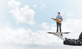 Businessman on metal tray playing acoustic guitar against blue sky background Stock Photo