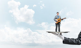 Businessman on metal tray playing acoustic guitar against blue sky background Royalty Free Stock Image