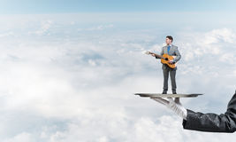 Businessman on metal tray playing acoustic guitar against blue sky background Stock Photography