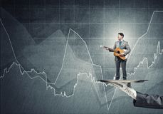 Businessman on metal tray playing acoustic guitar against concrete wall background with charts Stock Photo