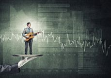Businessman on metal tray playing acoustic guitar against concrete wall background with charts Stock Image