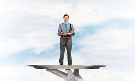 Businessman on metal tray playing drum blue sky background Royalty Free Stock Photos