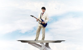 Businessman on metal tray playing electric guitar against blue sky background Stock Photography