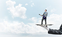 Businessman on metal tray playing electric guitar against blue sky background Royalty Free Stock Images