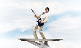 Businessman on metal tray playing electric guitar against blue sky background Stock Image
