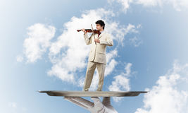 Businessman on metal tray playing violin against blue sky background. Hand of waiter presenting on tray man playing violin royalty free stock images