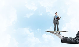 Businessman on metal tray with red book in hands against blue sky background Royalty Free Stock Photography