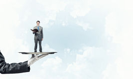 Businessman on metal tray with red book in hands against blue sky background Stock Image