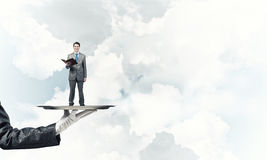 Businessman on metal tray with red book in hands against blue sky background Stock Images