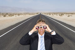 Businessman in middle of open road in desert, using binoculars, elevated view Stock Photography