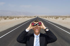 Businessman in middle of open road in desert, using binoculars, elevated view Stock Image