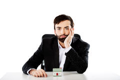 Businessman with a mini house in the office. Royalty Free Stock Photos