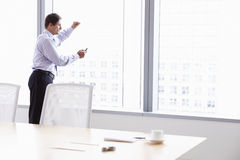 Businessman On Mobile Phone In Boardroom Stock Image