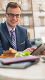 Businessman with mobile phone during breakfast. Royalty Free Stock Photo