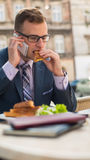 Businessman with mobile phone during breakfast. Royalty Free Stock Images