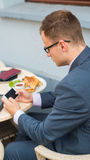 Businessman with mobile phone during breakfast. Stock Images