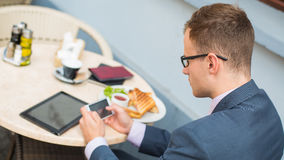 Businessman with mobile phone during breakfast. Stock Image