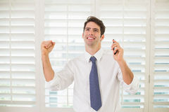 Businessman with mobile phone clenching fist in office Stock Photos