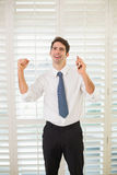 Businessman with mobile phone clenching fist in office Royalty Free Stock Photo