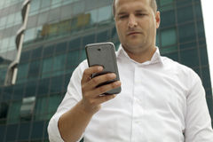 Businessman with a Mobile Phone. Front the Glass Building Royalty Free Stock Image
