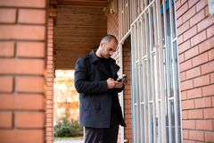Businessman with mobile phone in front of his office stock image