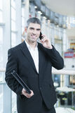 Businessman on mobile phone looking at camera Royalty Free Stock Image