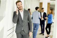 Businessman with mobile phone in office while other business people talking in background stock photos