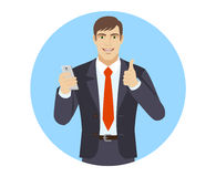 Businessman with mobile phone showing thumb up Stock Images