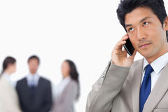 Businessman with mobile phone and team behind him Stock Image