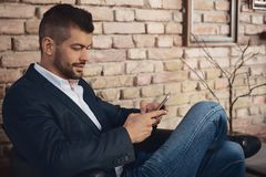 Businessman with mobilephone. Casual businessman using mobilephone in lobby Royalty Free Stock Image