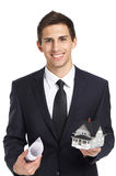 Businessman with model house and blueprint. Half-length portrait of businessman who hands model house and blueprint, isolated on white. Concept of real estate Stock Photography