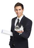 Businessman with model house and layout. Half-length portrait of businessman who hands model house and layout, isolated on white. Concept of real estate and Royalty Free Stock Photo