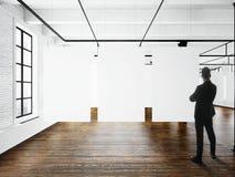 Businessman Modern art museum expo loft interior.Open space studio.Empty white canvas hanging.Wood floor,bricks wall Stock Images