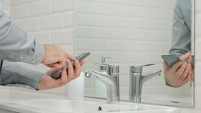 Businessman in Modern Bathroom Use Mobile Phone Accessing Online Urgent Messages.  royalty free stock images