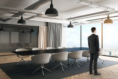 Businessman in modern boarding room. Side view of thoughtful young businessman standing in modern boarding room interior with furniture, curtains and city view royalty free stock photography