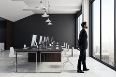Businessman in modern coworking office interior. Attractive european businessman standing in modern coworking office interior with equipment, furniture, city stock images