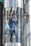 Businessman in modern glass elevator. Talking by the phone and holding papers Royalty Free Stock Images