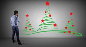 Businessman watching christmas trees sketch on a wall 3D renderi. Businessman in modern interior watching christmas trees sketch on a wall 3D rendering Stock Photo