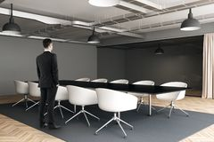 Businessman in modern meeting room. E view of thoughtful young businessman standing in modern meeting room interior with furniture. Think, research and stock images