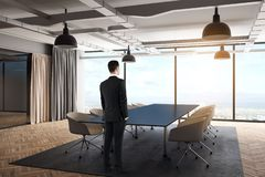 Businessman in modern meeting room. E view of thoughtful young businessman standing in modern meeting room interior with furniture, curtains and city view. Think stock photography
