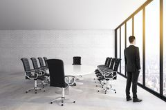 Businessman in modern meeting room. Thinking young businessman standing in modern meeting room interior with panoramic city view, furniture and daylight vector illustration