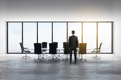 Businessman in modern meeting room. Thoughtful young businessman standing in modern meeting room interior with panoramic city view, furniture and daylight royalty free illustration