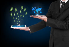 Businessman with modern mobile phone. Uploading map world data and  money flting out in his hand Stock Photography